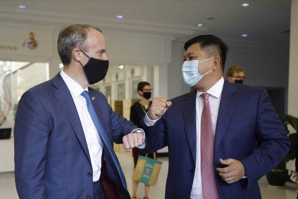 Britain's Foreign Secretary Dominic Raab, left, greets with an elbow bump with Cambodian's Environment Minister Say Sam Al after a meeting in Phnom Pe...
