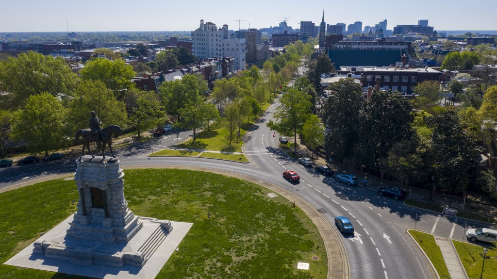 FILE - In this April 7, 2020 file photo sparse traffic winds around the statue of Confederate General Robert E. Lee on Monument Ave near downtown Rich...