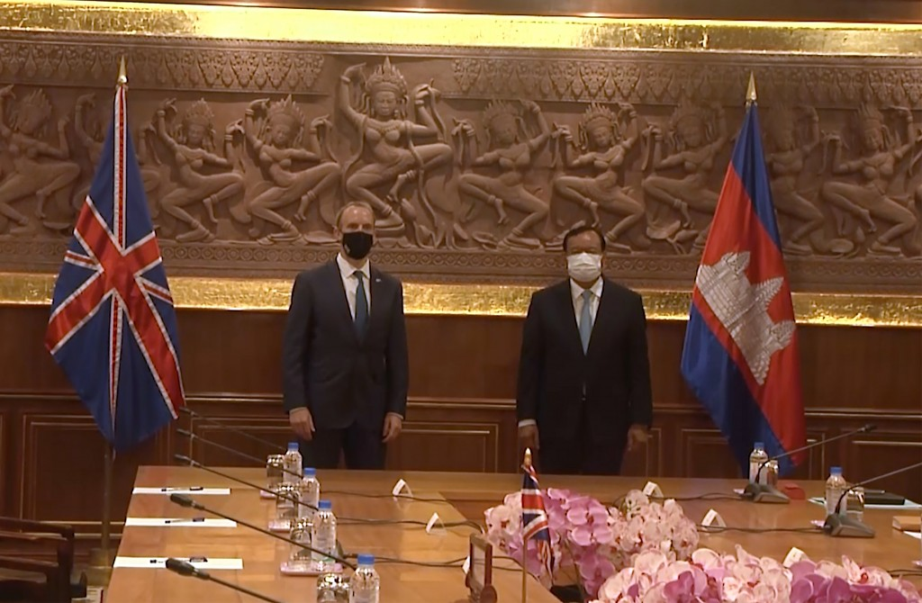 In this image made from video, Britain Foreign Secretary Dominic Raab, left, and  Cambodia Foreign Minister Prak Sokhonn greet each other while social...