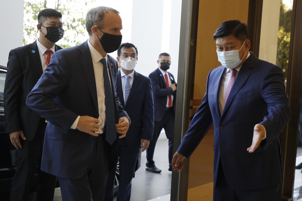 Britain's Foreign Secretary Dominic Raab, front left, meets Cambodian's Environment Minister Say Sam Al , right, on his arrival at Environment Ministr...