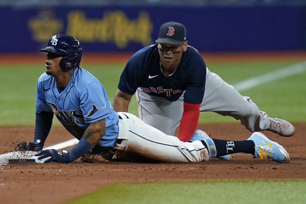 Tampa Bay Rays' Wander Franco, left, slides in safely to third base ahead of the tag by Boston Red Sox's Rafael Devers during the sixth inning of a ba...