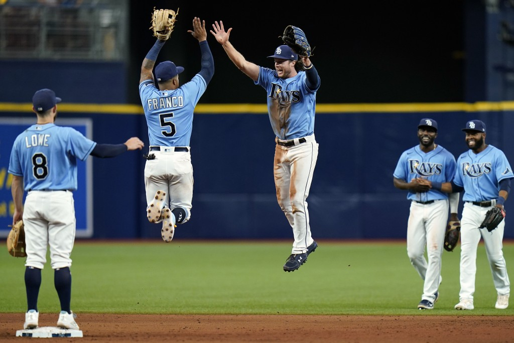 Tampa Bay Rays shortstop Wander Franco (5) and center fielder Brett Phillips celebrate with teammates after defeating the Boston Red Sox during a base...