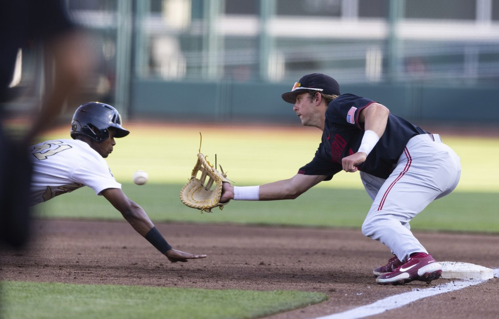 Stanford's Nick Brueser (24), right, tags out Vanderbilt's Enrique Bradfield Jr (51) on a dive back to first base in the first inning during a basebal...