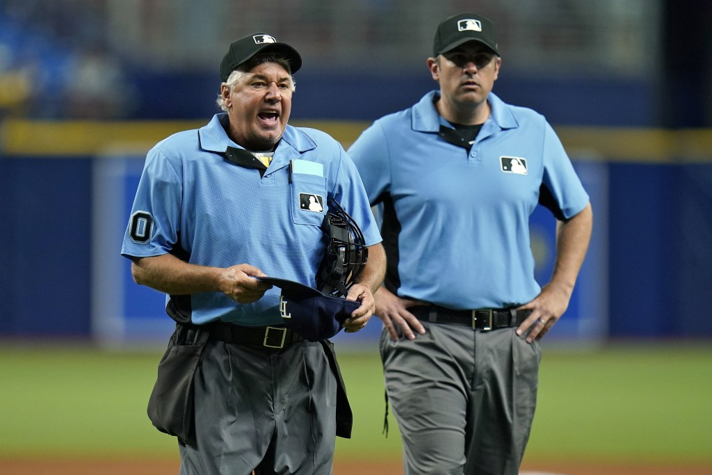 Home plate umpire Tom Hallion, left, makes Tampa Bay Rays relief pitcher Diego Castillo change his hat during the ninth inning of a baseball game Wedn...