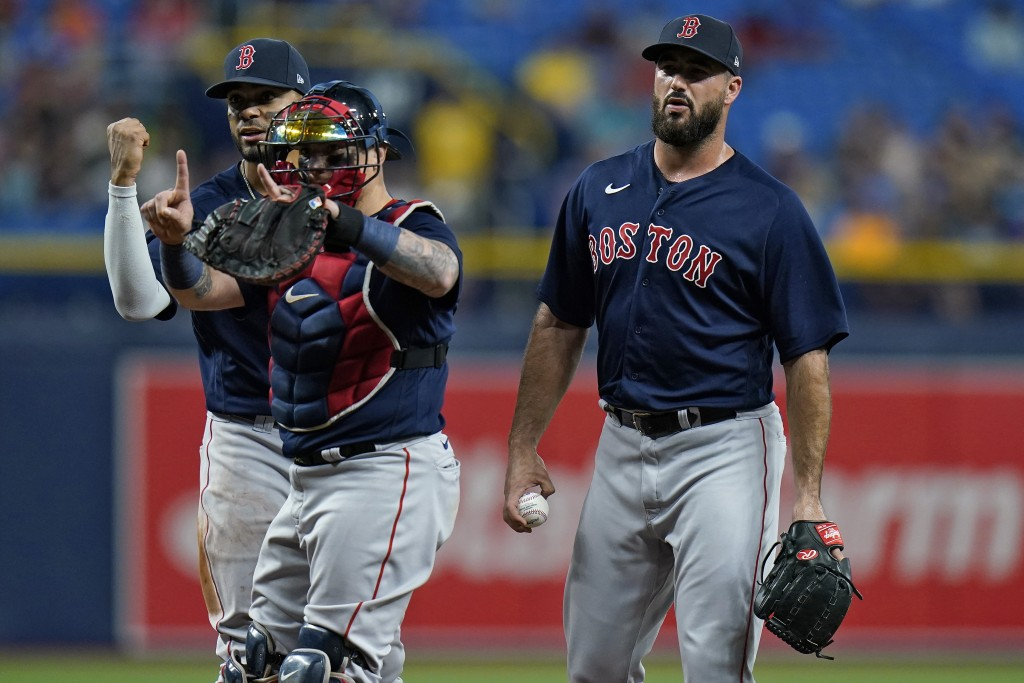Boston Red Sox plyers, from left, third baseman Rafael Devers, catcher Christian Vazquez, and relief pitcher Brandon Workman react after Workman was c...