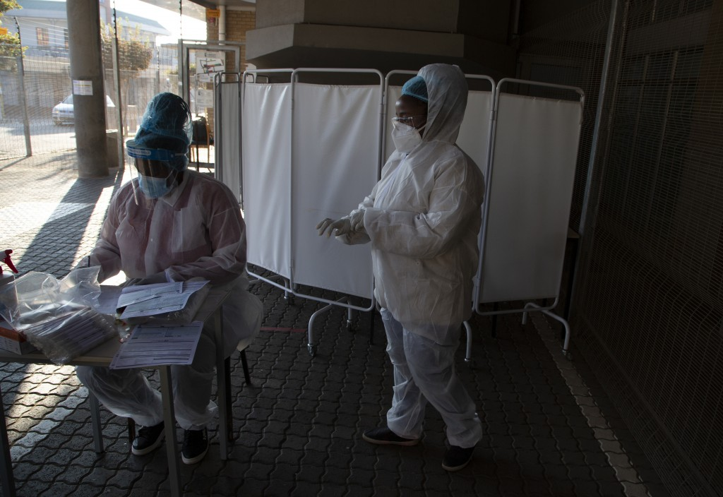 FILE - In this Tuesday, June 22, 2021 file photo, healthcare workers prepare to test patients for COVID-19 at the Lancet Laboratories in Johannesburg....