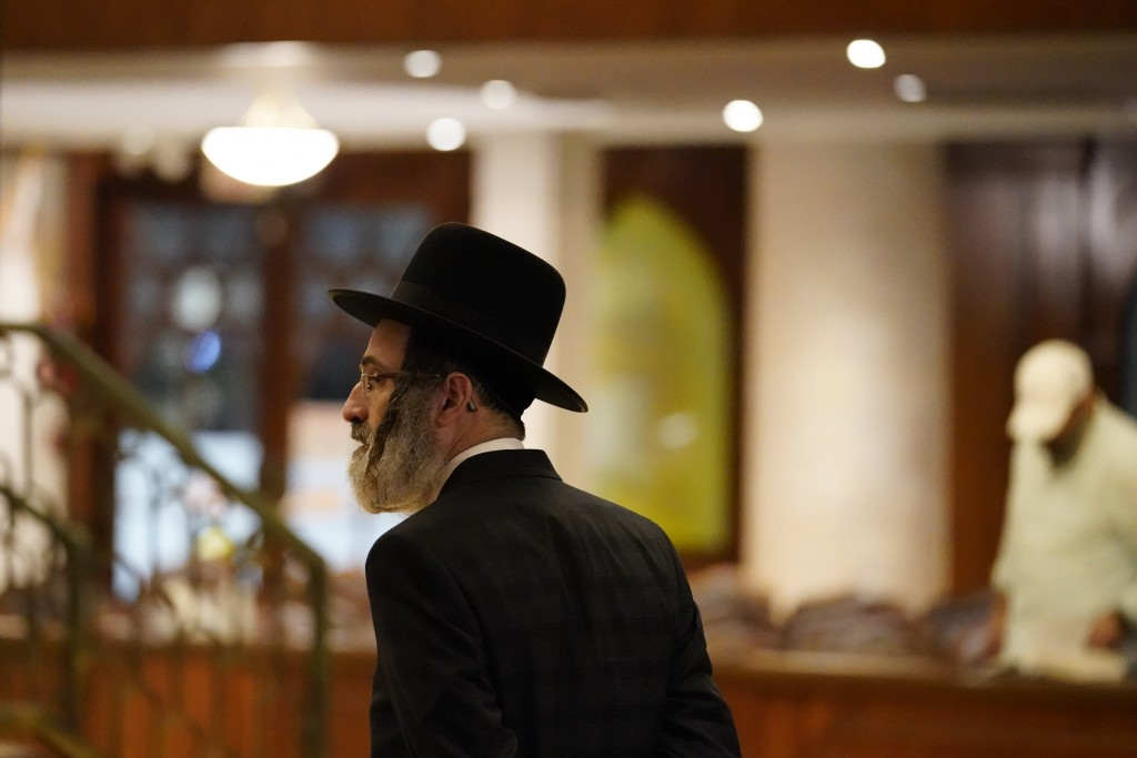 An Orthodox Jewish man walks inside the Shul of Bal Harbour where worshippers were praying after members of the community were reported missing in the...