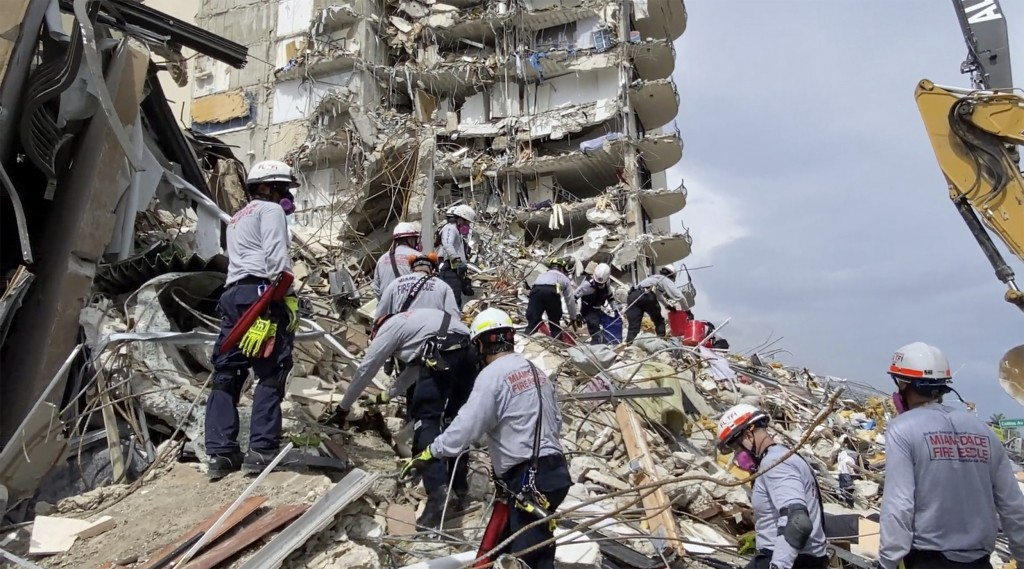 This photo provided by Miami-Dade Fire Rescue, search and rescue personnel search for survivors through the rubble at the Champlain Towers South Condo...