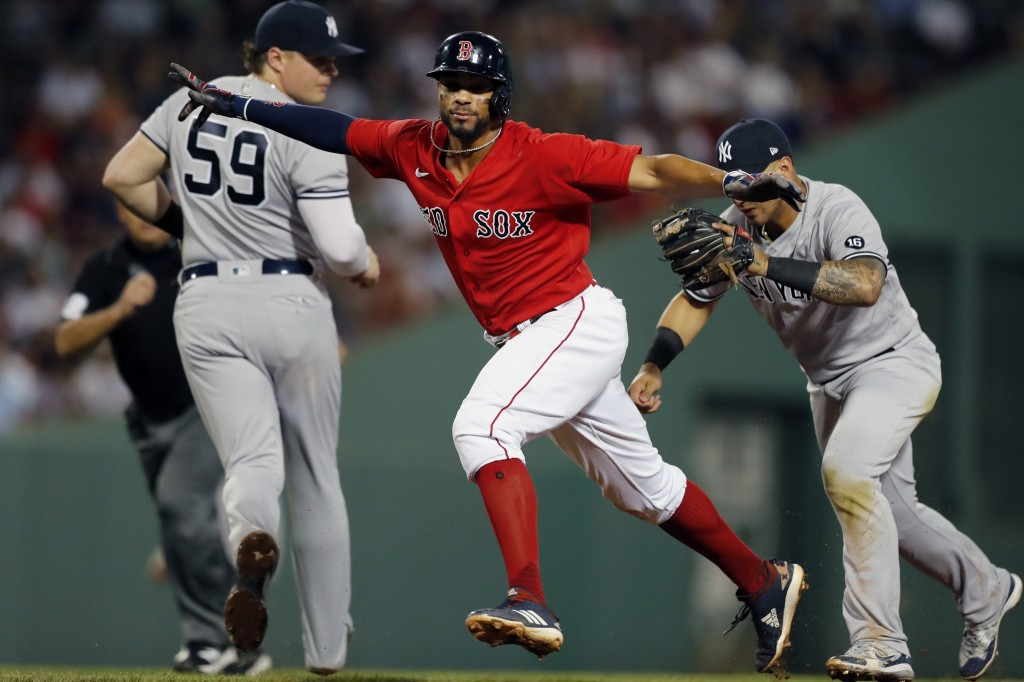 Boston Red Sox's Xander Bogaerts, center, is caught in a rundown by New York Yankees' Gleyber Torres, right, after Rafael Devers grounded into a doubl...
