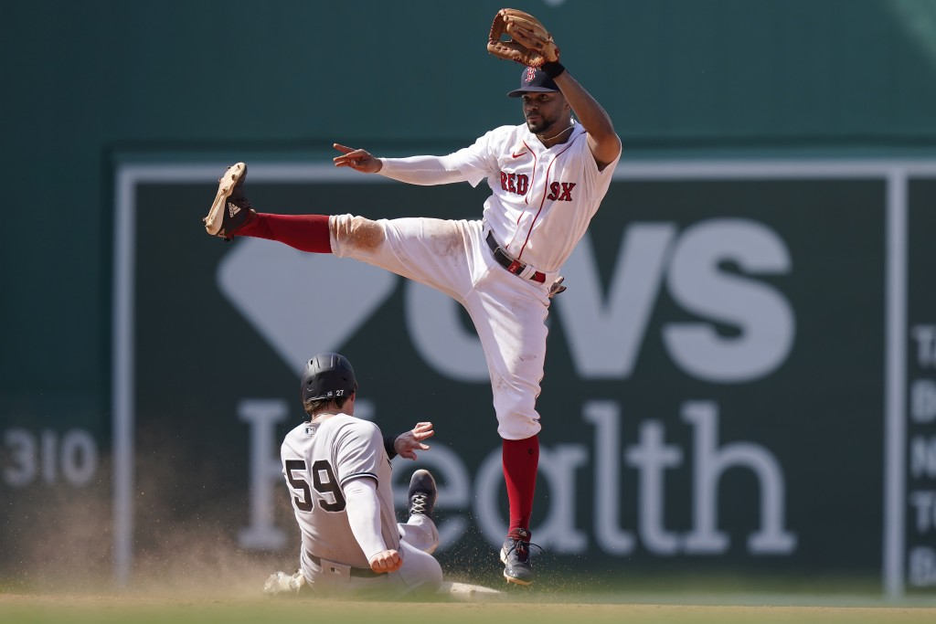 New York Yankees' Luke Voit (59) slides out at second base as Boston Red Sox's Xander Bogaerts follows through on a throw to first to complete a doubl...