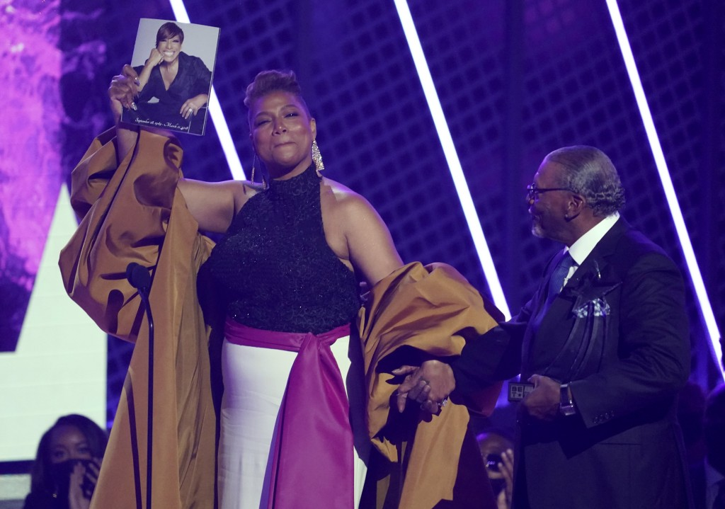 Queen Latifah, winner of the lifetime achievement award, holds a photo of her late mother Rita Owens as she walks with her father Lancelot Owens, Sr. ...