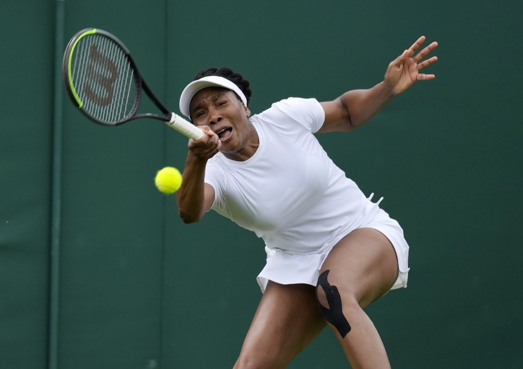 Venus Williams of the US plays a return to Romania's Mihaela Buzarnescu during the women's singles first round match on day two of the Wimbledon Tenni...
