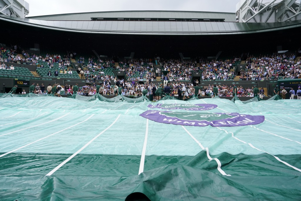 The rain covers are pulled over No. 1 Court during a rain delay on day two of the Wimbledon Tennis Championships in London, Tuesday June 29, 2021. (AP...
