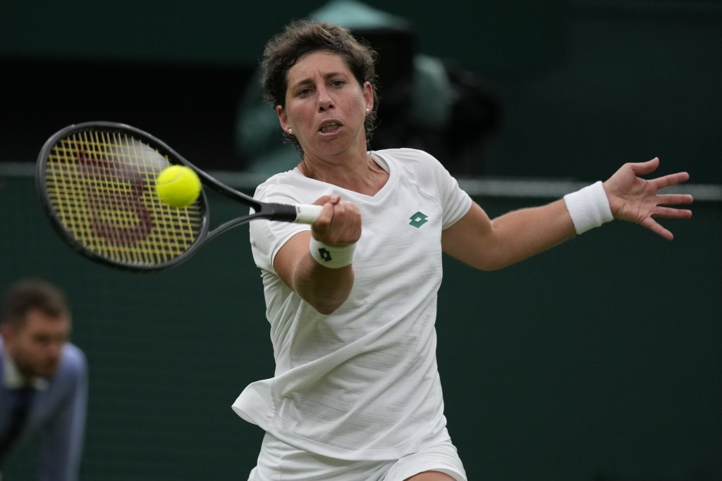 Spain's Carla Suarez Navarro plays a return to Australia's Ashleigh Barty during the women's singles first round match on day two of the Wimbledon Ten...