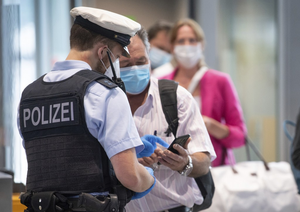 Federal police officers check passengers arriving aboard a flight from Portugal, at Frankfurt airport Tuesday June 29, 2021. As of Tuesday, Portugal i...