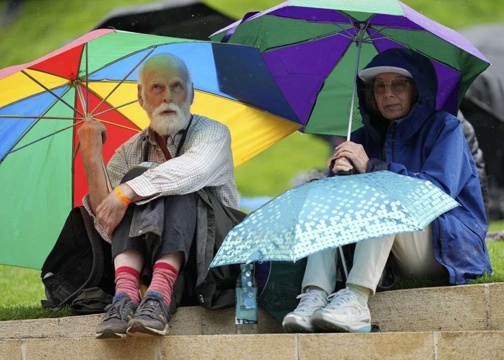 People shelter under umbrellas during a rain delay on day two of the Wimbledon Tennis Championships in London, Tuesday June 29, 2021. (AP Photo/Albert...