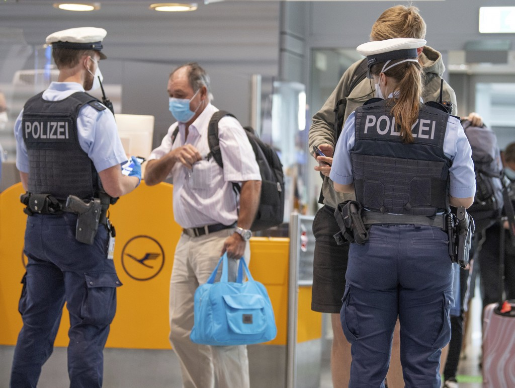 Federal police officers check passengers arriving aboard a flight from Portugal, at Frankfurt airport, Germany, Tuesday June 29, 2021. As of Tuesday, ...