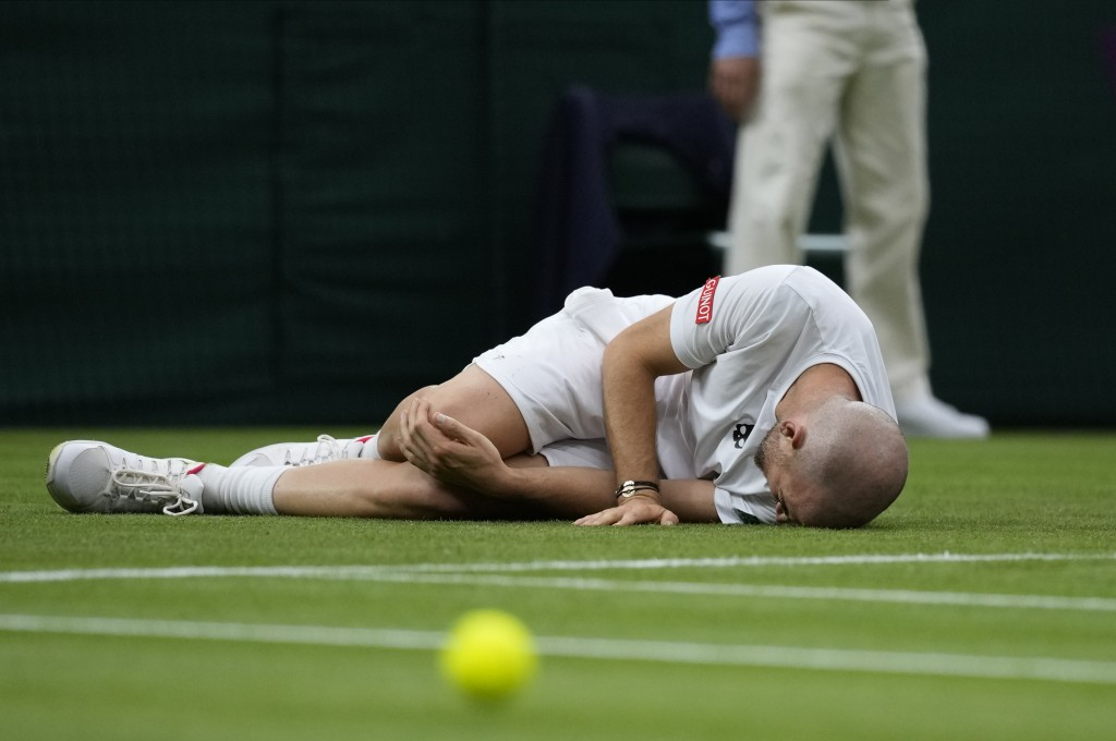 Adrian Mannarino of France lies on the ground in pain during the men's singles first round match against Switzerland's Roger Federer on day two of the...