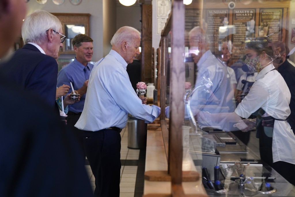 President Joe Biden buys ice cream at The Pearl Ice Cream Parlor Tuesday, June 29, 2021, in La Crosse, Wis., as Wisconsin Gov. Tony Evers, left, watch...