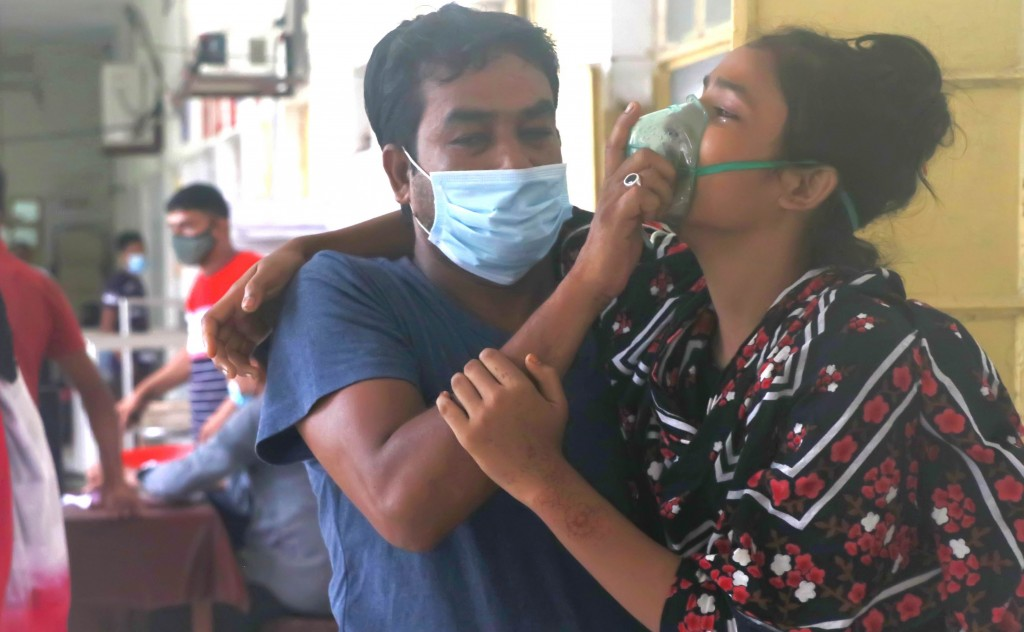 A man assists a patient facing difficulties in breathing at the Medical College Hospital in Rajshahi, 254 kilometers (158 miles) north of the capital,...