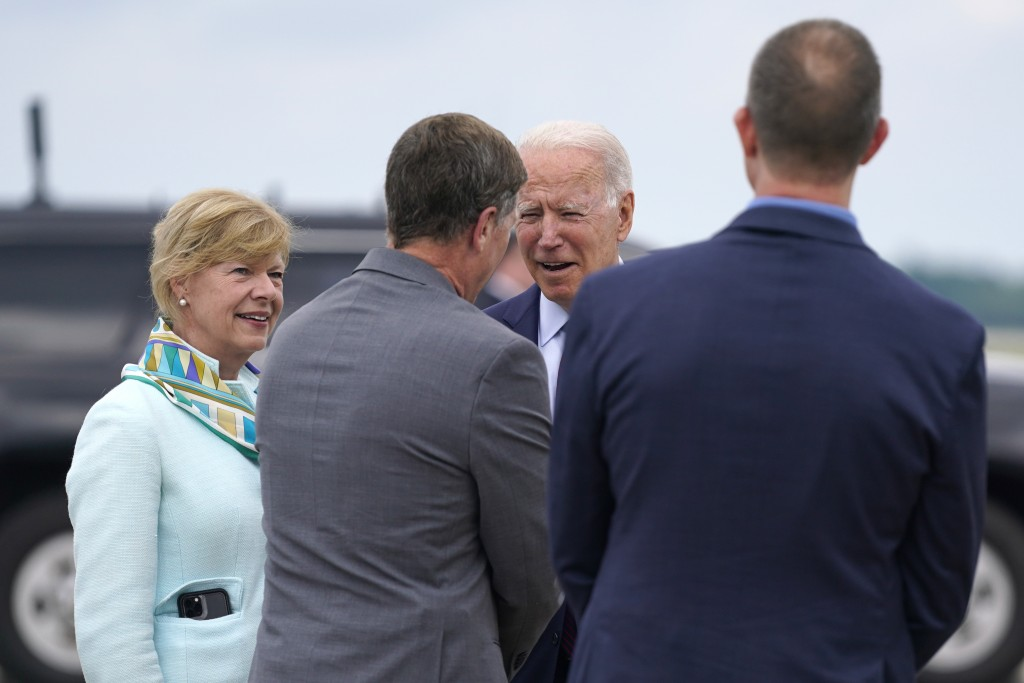 President Joe Biden talks with Rep. Ron Kind, D-Wis., center, Sen. Tammy Baldwin, D-Wis., left, and La Crosse Mayor Mitch Reynolds as he arrives on Ai...
