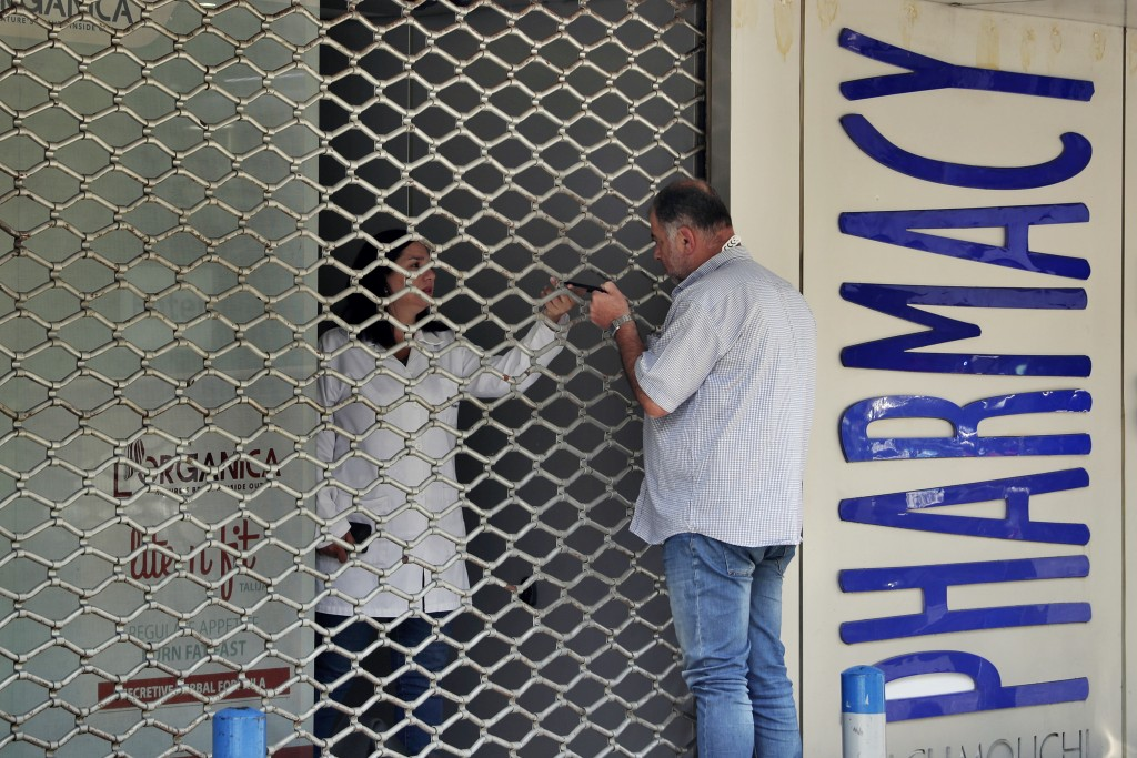 FILE - In this June 11, 2021 file photo, a man speaks with a pharmacist through a closed door after Pharmacies across Lebanon began a two-day strike p...