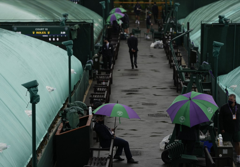 Outside courts are covered during a rain delay on day two of the Wimbledon Tennis Championships in London, Tuesday June 29, 2021. (AP Photo/Alastair G...