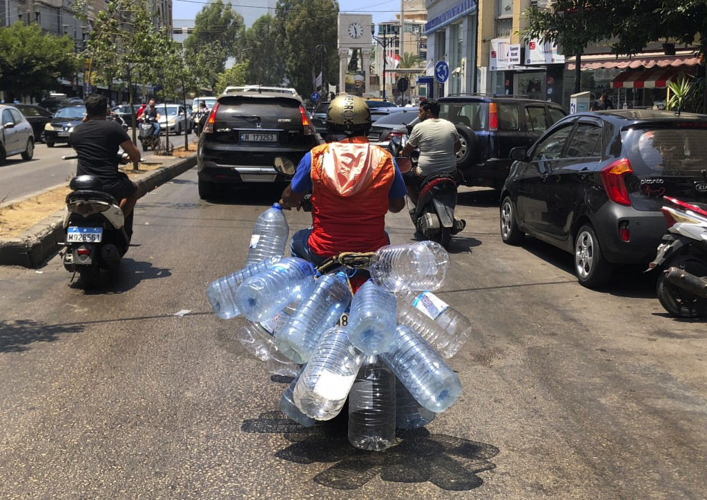 A man rides his scooter with empty water bottles to fill them with gasoline, in Beirut, Lebanon, Wednesday, June 23, 2021. Lebanon is struggling amid ...