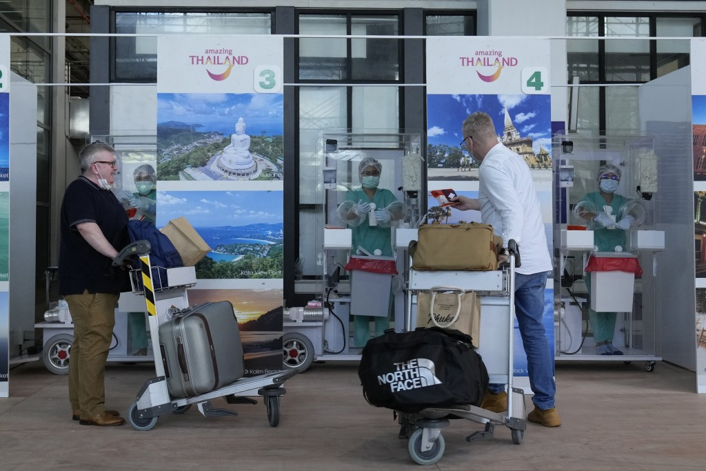 The first group of tourists prepare for a COVID-19 swab test after arriving at the Phuket International Airport in Phuket, southern Thailand, Thursday...