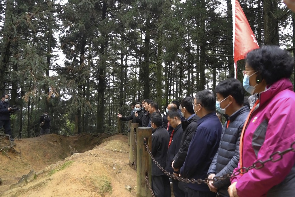 Students at the China Executive Leadership Academy listen to a field lecture in front of revolutionary wartime trenches of the late 1920s in JInggangs...