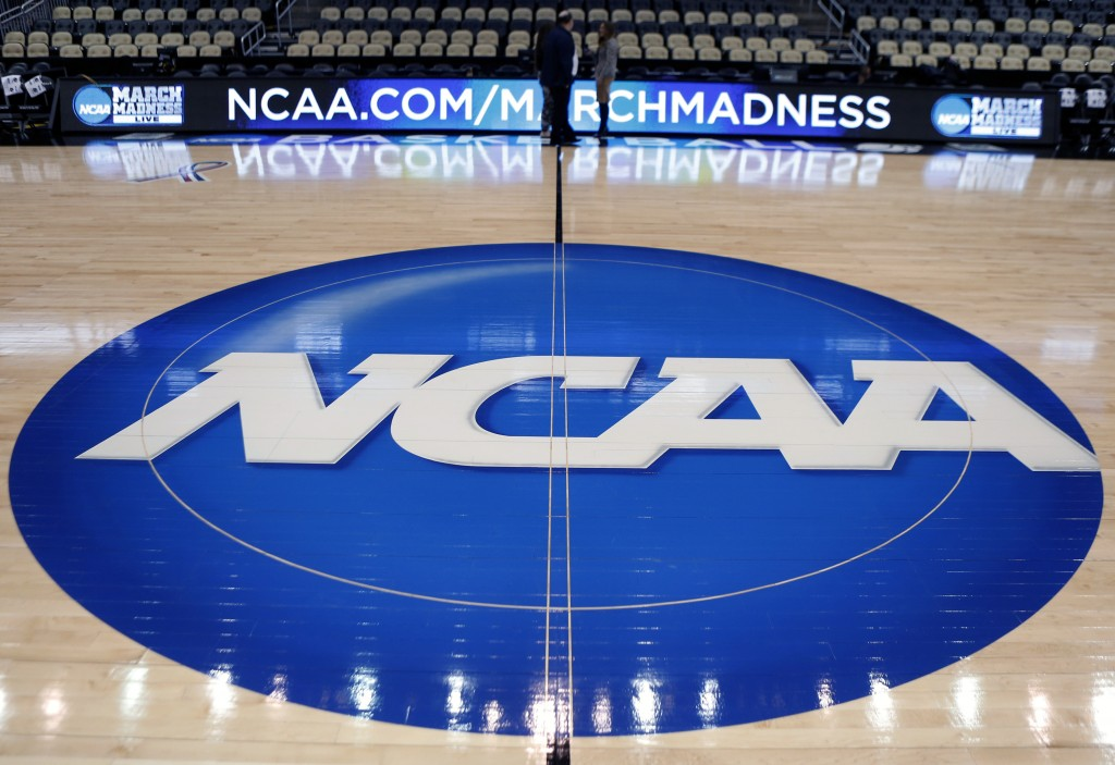 FILE - In this March 18, 2015, file photo, the NCAA logo is displayed at center court as work continues at The Consol Energy Center in Pittsburgh, for...