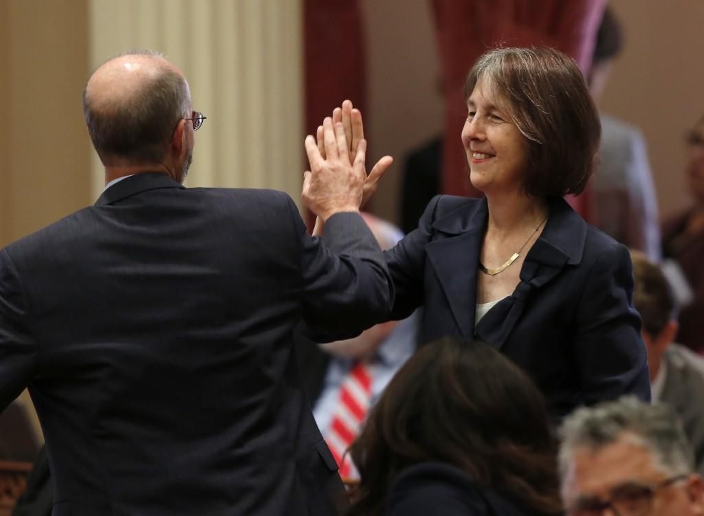 FILE - Sen. Nancy Skinner, D-Berkeley, and Sen. Steven Glazer, D-Orinda slap palms in celebration after her measure to let athletes at California coll...