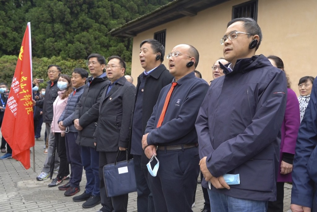 Students at the China Executive Leadership Academy recite a poem by revolutionary leader Mao Zedong in front of a wartime military outpost in Jinggang...