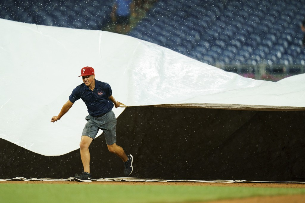 A member of the Philadelphia Phillies' grounds crew helps cover the field for a rain delay during the fifth inning of the Phillies' baseball game agai...