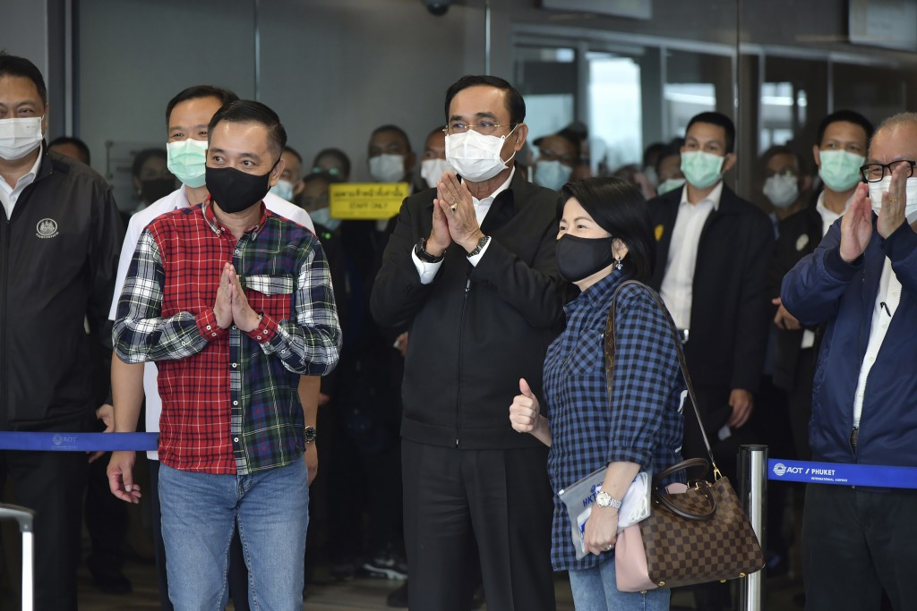 In this photo released by the Thailand Government Spokesman's Office, Thailand's Prime Minister Prayuth Chan-ocha, center, welcome tourists arriving f...