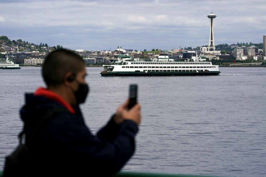 File-In this May 25, 2021 file photo a passenger wears a mask while riding on a Washington state ferry from Bremerton to Seattle as another ferry pass...