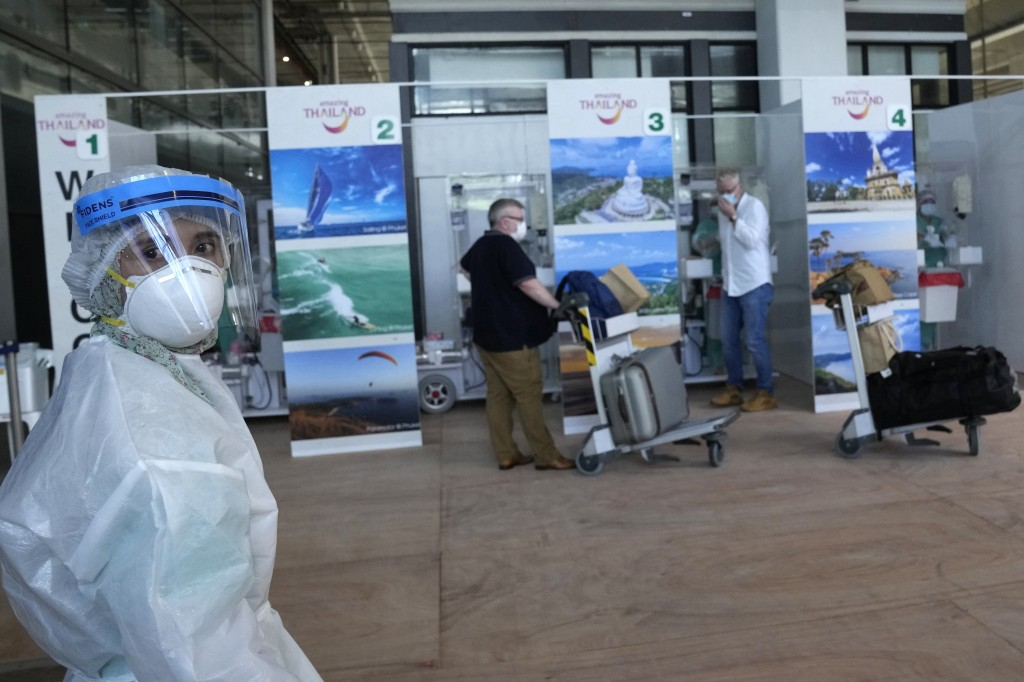 The first group of tourists receive a swab test for the COVID-19 after arriving at the Phuket International Airport in Phuket, southern Thailand,Thurs...
