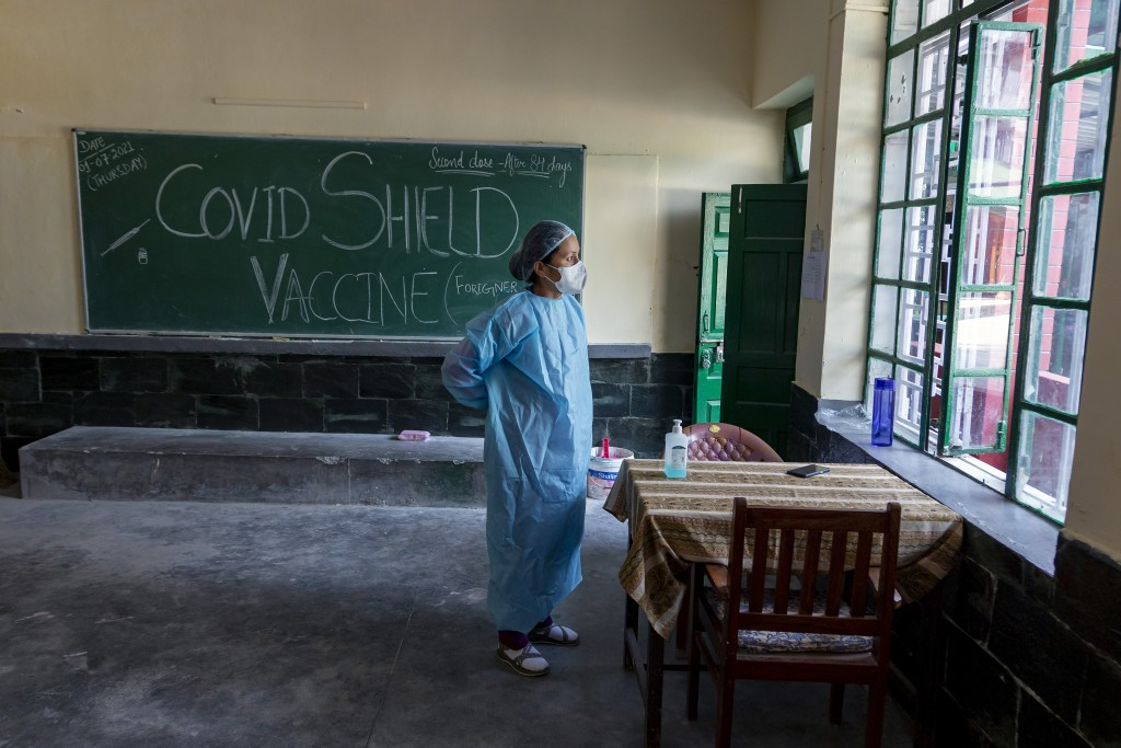 An exile Tibetan nurse puts on her protective suit as she prepares to assist at a COVID-19 vaccination center in Dharmsala, India, Thursday, July 1, 2...
