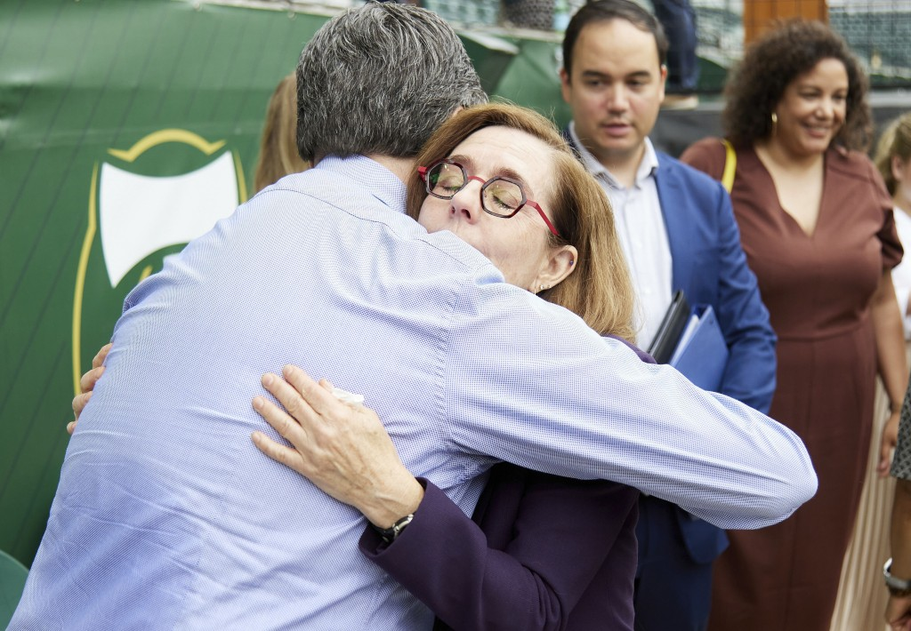 Oregon Governor Kate Brown, right, hugs an employee of the Oregon Health Authority after announcing the end of the state's COVID-19 restrictions in Po...