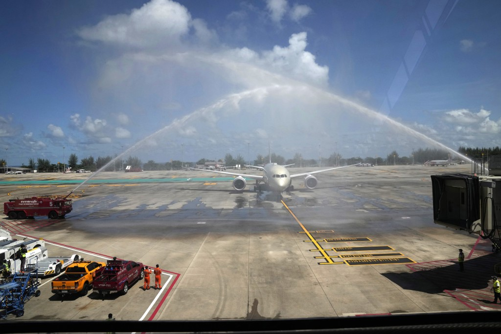 A flight from Abu Dhabi carrying the first group of international tourists to Phuket is ceremoniously showered with water as it arrives at the airport...