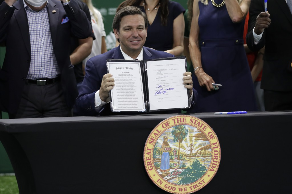 FILE - Florida Gov. Ron DeSantis holds up a just signed bill which would allow college athletes in the state to earn money from endorsement deals, at ...
