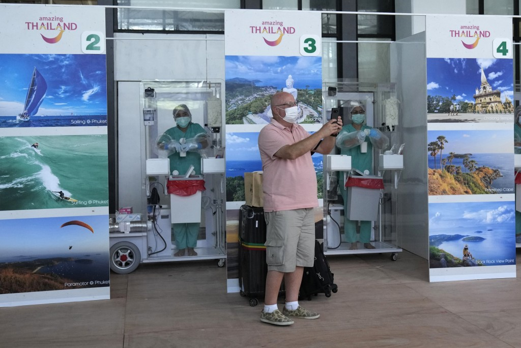 A tourist take a picture after a COVID-19 swab test after arriving at the Phuket International Airport in Phuket, southern Thailand,Thursday, July 1, ...