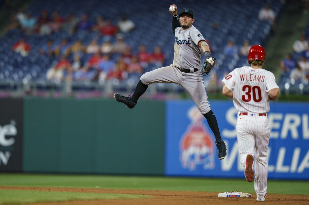 Miami Marlins shortstop Miguel Rojas leaps after getting the force out on Philadelphia Phillies' Luke Williams, right, during the eighth inning of a b...