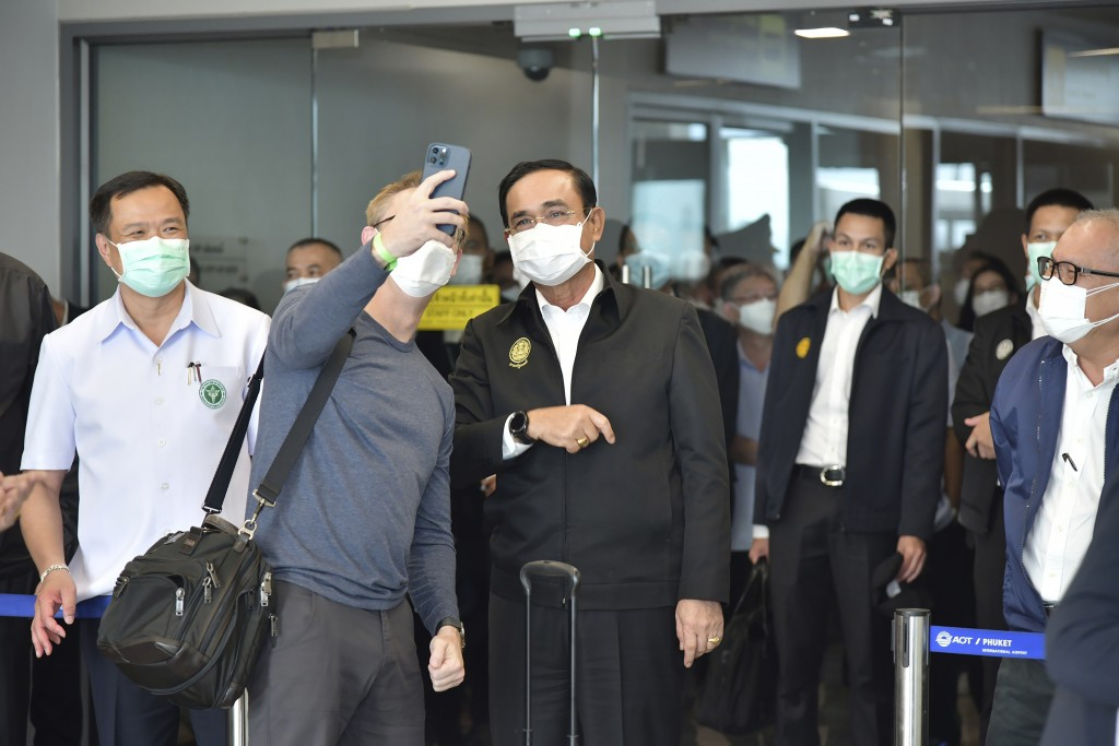 In this photo released by the Thailand Government Spokesman's Office, tourists take selfies with Thailand's Prime Minister Prayuth Chan-ocha, center, ...