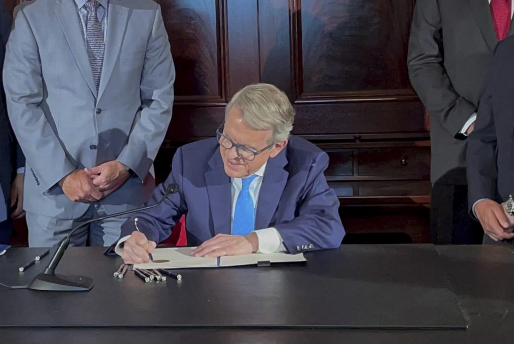 FILE - Ohio Governor Mike DeWine signs an executive order allowing college athletes in Ohio to earn money off their name, image and likeness at the Oh...