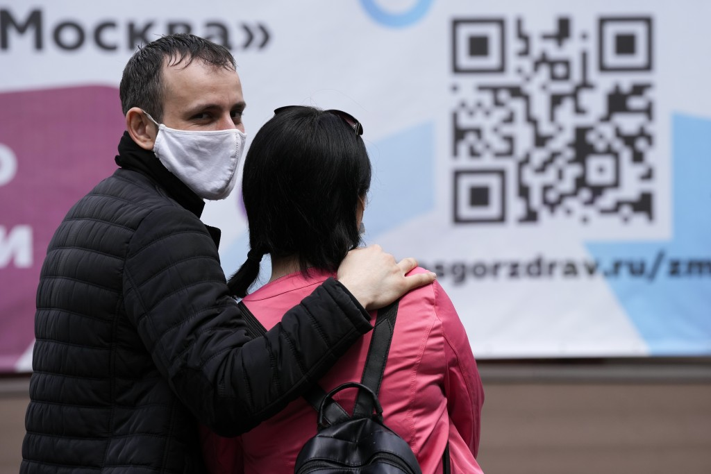 A couple wait in line to receive a coronavirus vaccine at a vaccination center with the sign of a QR code at VDNKh (The Exhibition of Achievements of ...