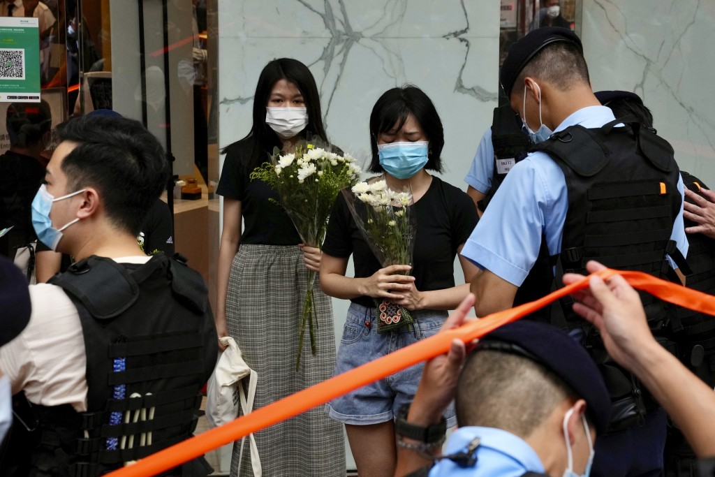 People hold flowers to mourn the death of an assailant who stabbed a police officer in Hong Kong.