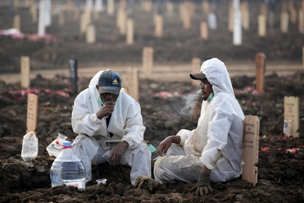 Workers take a break during a busy day at Rorotan Cemetery, which is reserved for those who died of COVID-19, in Jakarta, Indonesia, Thursday, July 1,...