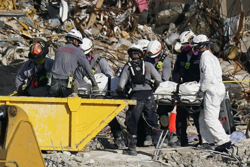 Search and rescue personnel remove remains on a stretcher as they work atop the rubble at the Champlain Towers South condo building where scores of pe...