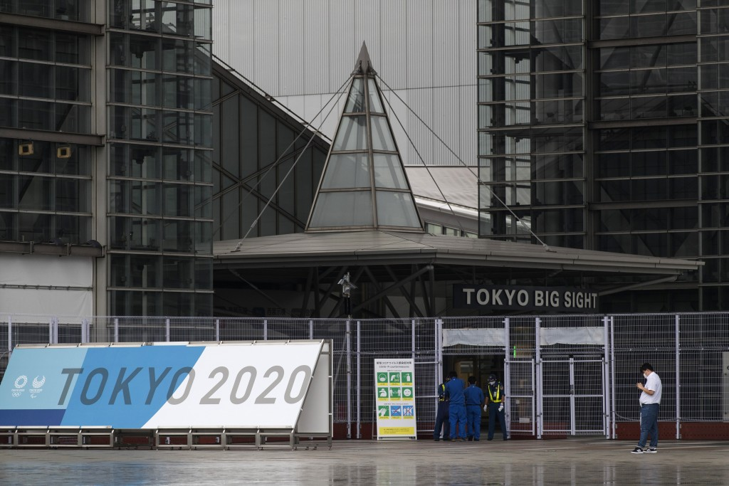 Security guards check ID cards and temperatures of workers as they enter a convention center housing the main media center of the Olympic and Paralymp...